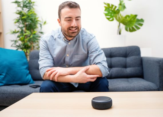 Man using an echo dot virtual assistant